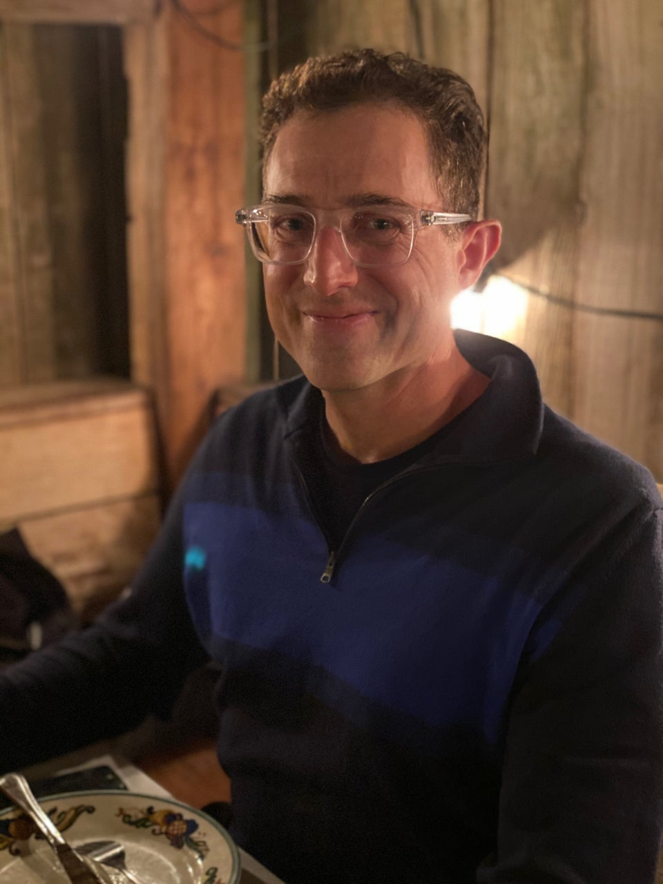 Tantek smiling in the Zazie patio in the evening, lit by lamps, wearing a half-zip dark blue sweater with a medium blue wide stripe across it.