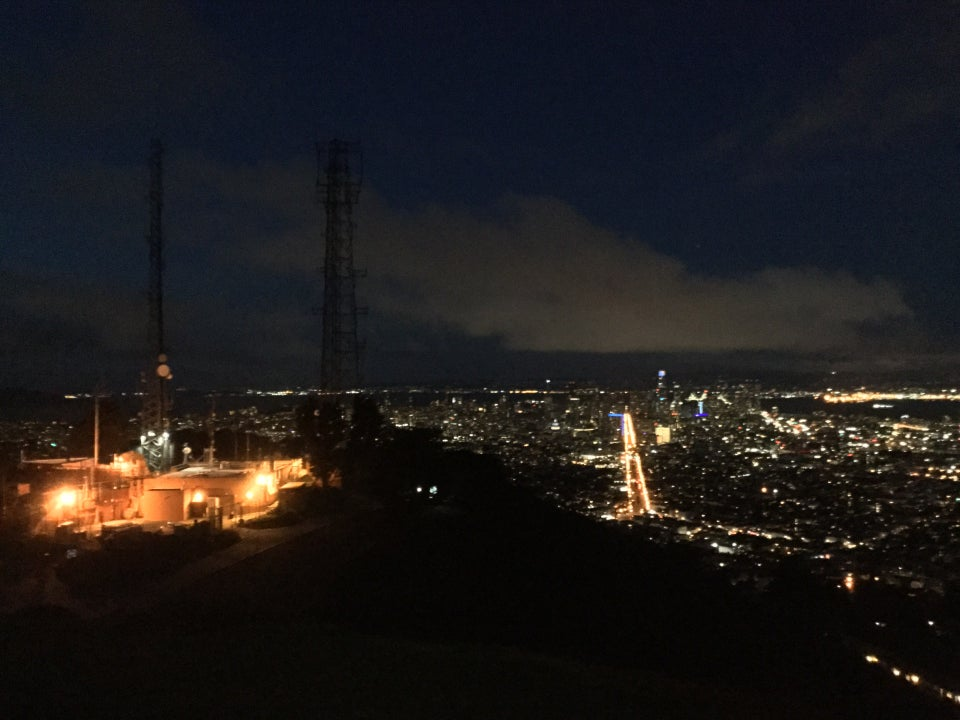 A large white cloud on a very dark blue sky underlit by city lights, most prominently two segments from streetlights outlining the edges of Market street converging in the distance, a dark hill in the foreground, to the left the top of Twin Peaks and its few utility buildings lit with a few lights, two thin dark transmission towers rising above them.