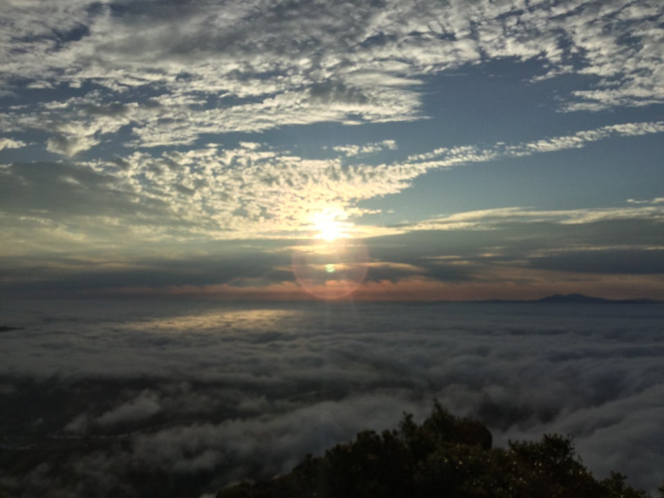 Sun rising above a few layers of clouds viewed from the Mount Tam East Peak