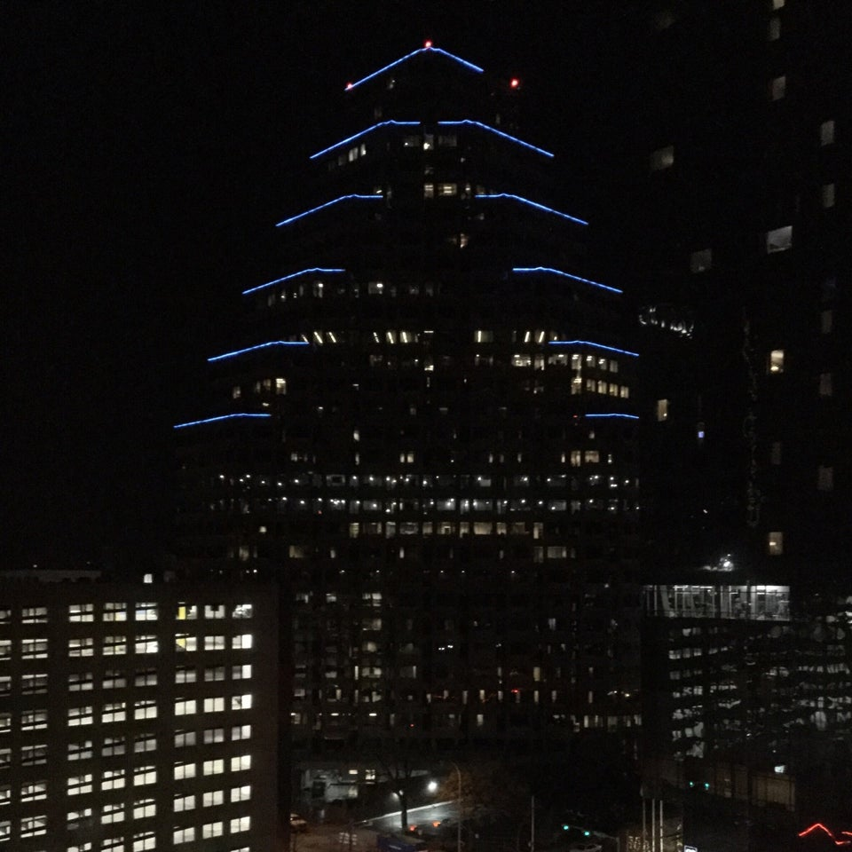 Building with pyramid shaped terraces at night, with blue lights glowing on each of the terrace corners. a few more downtown Austin buildings at night.