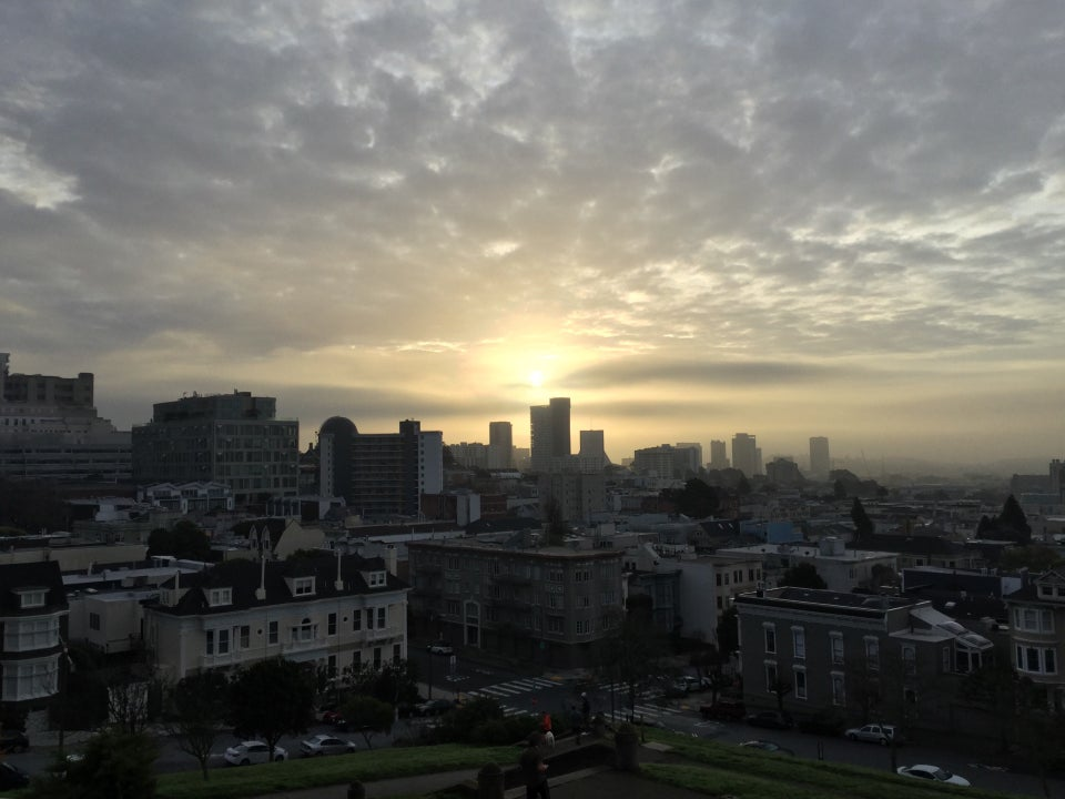 The sun peaking through thick clouds over San Francisco, above Alta Plaza Park