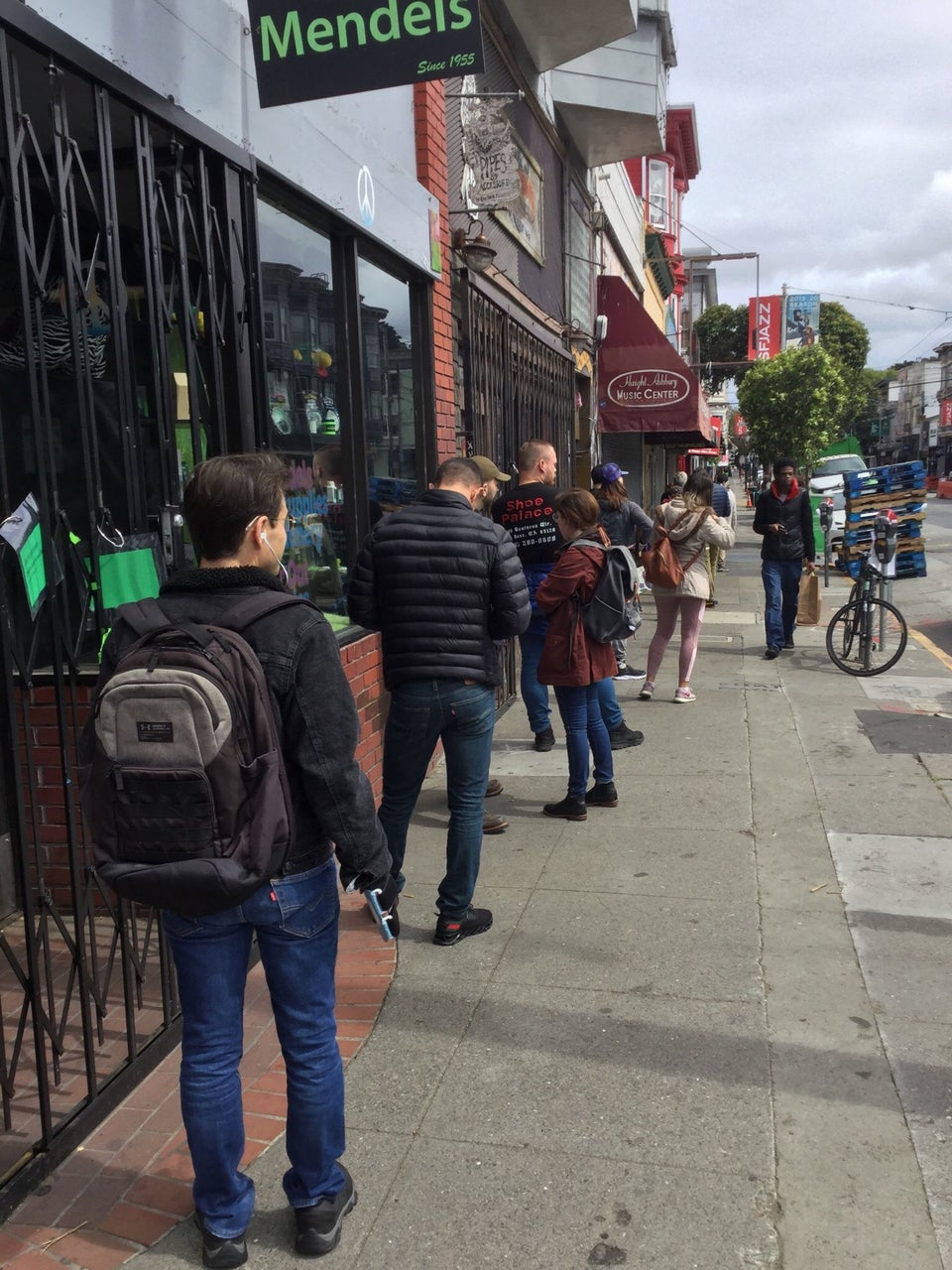 Line of people on the sidewalk on Haight Street, approximately six feet apart from each other, waiting to get into Haight Street Market.