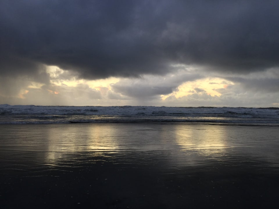 Dark storm clouds with just a few gaps behind them where the light sky shined down, showing a reflecting on wet sand in front the waves at Ocean Beach.