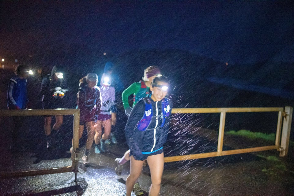 Half a dozen runners wearing headlamps, rain gear, and shorts, starting a run crossing through a gate in the darkness, their headlamps lighting up the pouring rain, Rodeo Beach in the background.