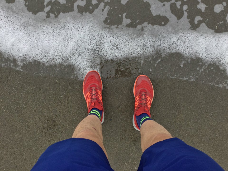 Looking down shorts and trail shoes standing on the beach, the surf receding