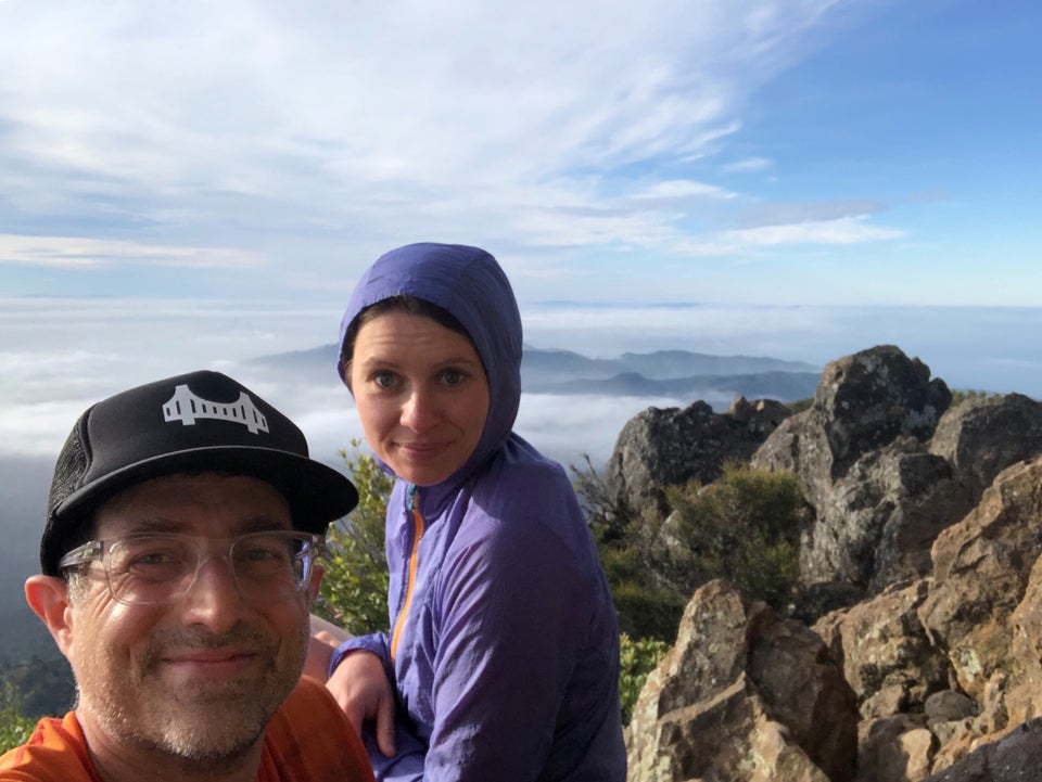 Tantek and Hannah sitting on top of Mt. Tam, bushes and rocks right behind them, clouds and hills below in the distance, partially visible San Francisco building tops poking through thick fog in the far distance