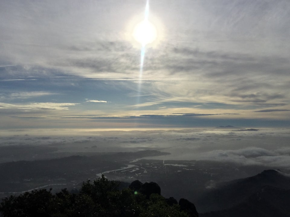 The sun shining through an upper cloud layer, high above distant mountain peaks, themselves poking through lower clouds, a partially visible bay, and nearer hills, bushes and a rocky outcropping in the foreground